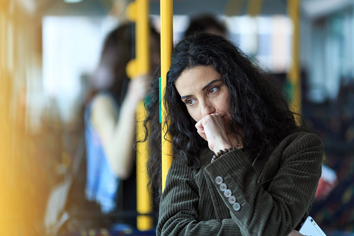 Pensive young woman traveling with bus and holding smart phone. Wears casual clothes.