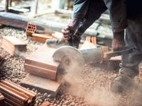Industrial construction worker using a professional angle grinder for cutting bricks and building interior walls